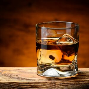 whiskey-with-ice-on-a-wooden-table-thorne-travel-kilwinning